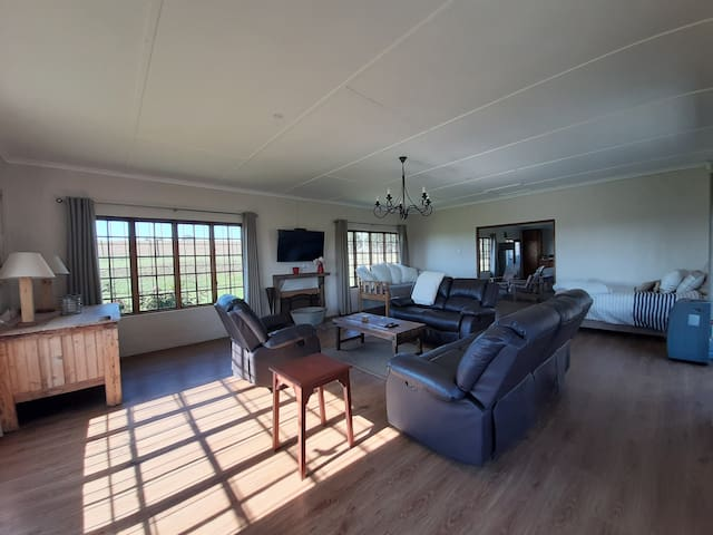 Lounge with spectacular views of the berg. There is also a lovely fireplace and tv with a full dstv package. In the far corners there is a 3 quarter bed and a sleeper couch