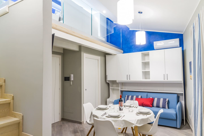 Living Room: sofa bed, dining table, Smart TV, air conditioning, interior details, central heating.  Salotto: divano letto, tavolo da pranzo, Smart TV, aria condizionata (A/C) , dettagli interni, riscaldamento.