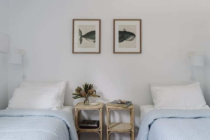 Bruny Boathouse Twin Room | cloud soft cotton and flax linen sheets & bedding.   Beds can be configured to a king bed upon request. A bed rail is also in the top shelf of cupboard for little ones to prevent tumbles in the night.