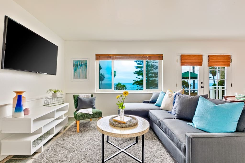 Beach inspired decor in this comfortable living room with an ocean view and large flat screen TV.