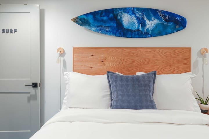 A custom painted surfboard, wood headboard, and accent lighting complete this Surf Room!