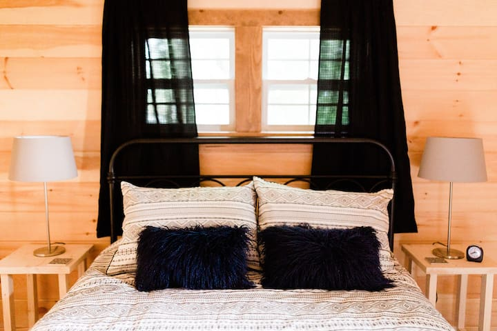 Queen sized Bed below windows facing the creek! Crack them open to enjoy the sounds of the water while you rest!