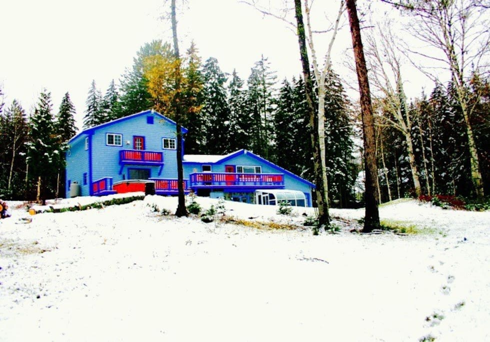 A winter view of Xanadu House, set on a small hill looking down at the pond and Bigelow Mountain,