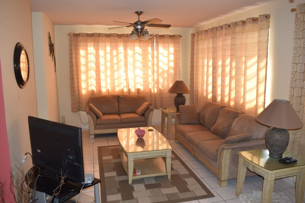 Large living room, with comfortable seating for 4 and TV with cable.
