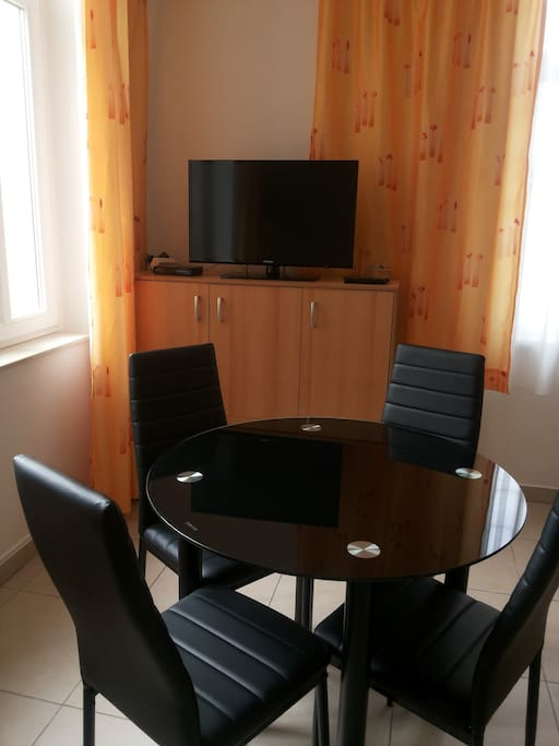 Main room, living and dining room, bedroom, folding couch and kitchen table, flat TV