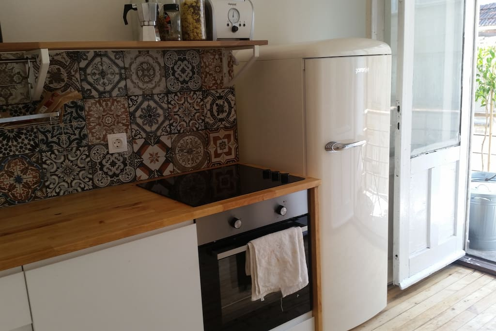 Kitchen: washing machine, dryer, oven, hot plates, fridge.