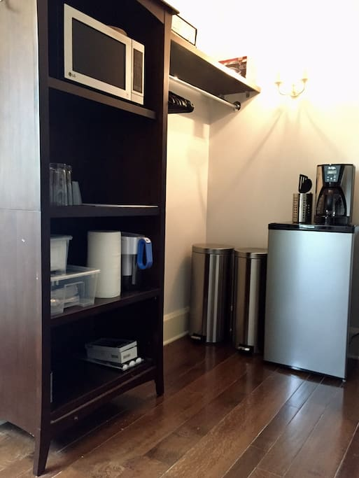 Large walk in closet includes food prep area with microwave, mini fridge, mobile cart with cutting board surface, coffee maker and other kitchen amenities.