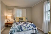 The bright master bedroom has a queen-size bed