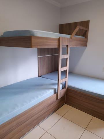 Suíte 2  c/ 3 camas tipo beliche, cortina blackout e ar-condicionado split.