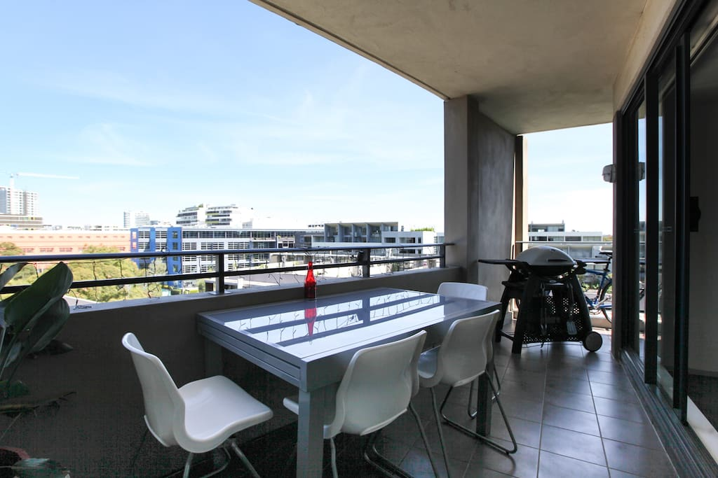 Balcony with seating and bbq with views of the city and surrounding area.