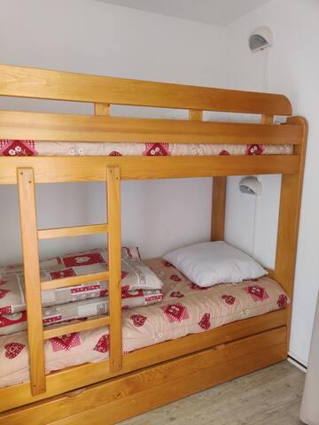 Lits superposés  dans la chambre + 1 lit d'appoint. Petite fenêtre avec volet.