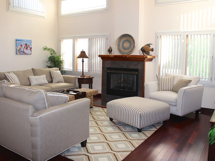 The great room has cathedral ceilings, hardwood flooring, & new furniture.