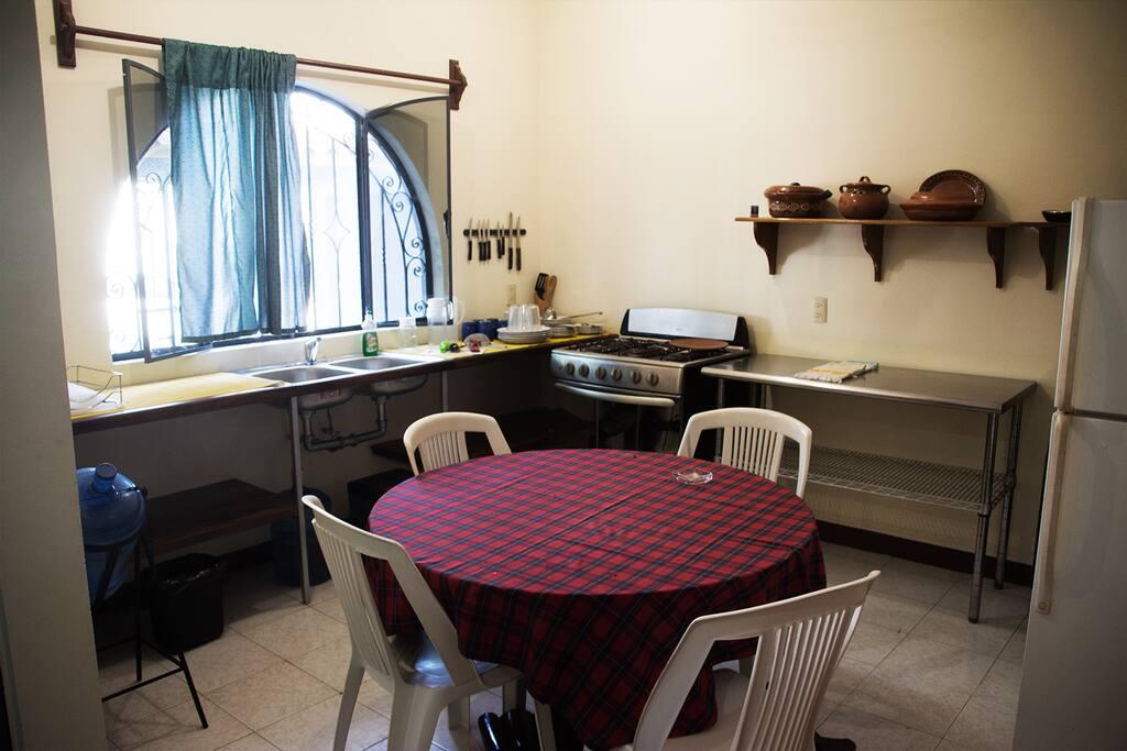 Cocina equipada con estufa con horno, refrigerador, vajilla, así como utensilios de cocina y ventilador.