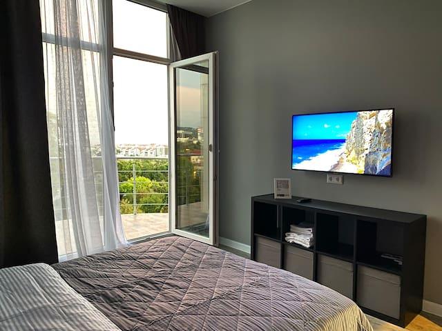 Спальня#1 с большой кроватью (160/200), 4kUHD телевизор и выходом на балкон-террасу с видом на Олимпийский парк