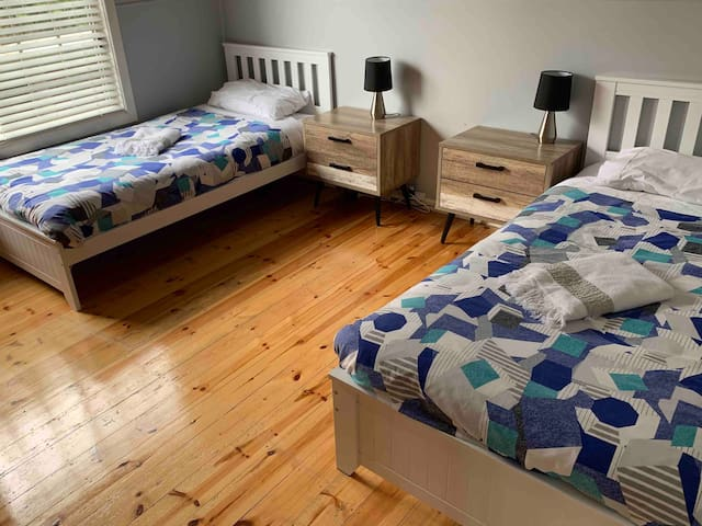 The third bedroom has two single beds, a tallboy and wardrobes.