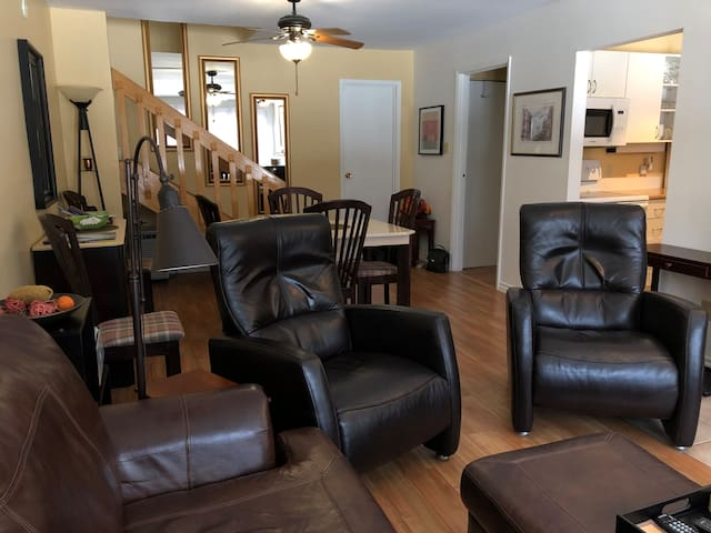 Split level entrance - view of living room with hardwood floor, leather recliners and couch + dining room with 6 chairs.  View away from windows.