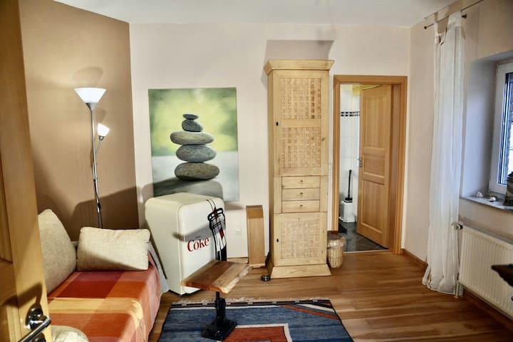 Das Zimmer kann bei einem einzelnen Gast als Wohnzimmer genutzt werden. Es verfügt u.a. über einen Kleiderschrank und einen Fernseher. Bei zwei Gästen lässt sich die Schlafcouch zu einem Bett (1,40c2,00) mit bequemen Topper umbauen.