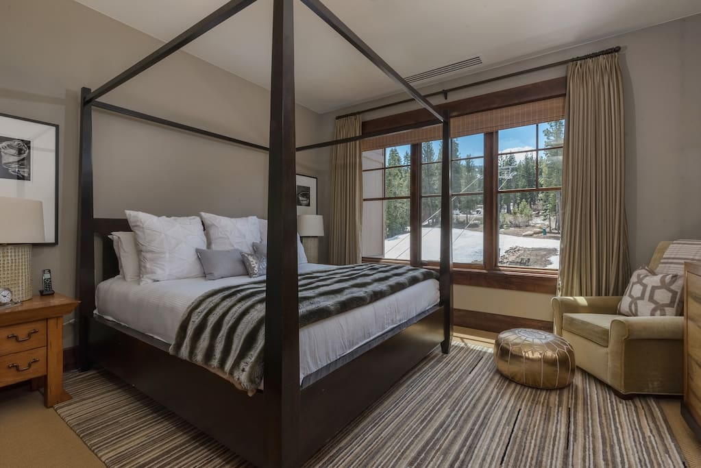 A regal king-size bed in a master bedroom with views looking directly over the ski run and gondola
