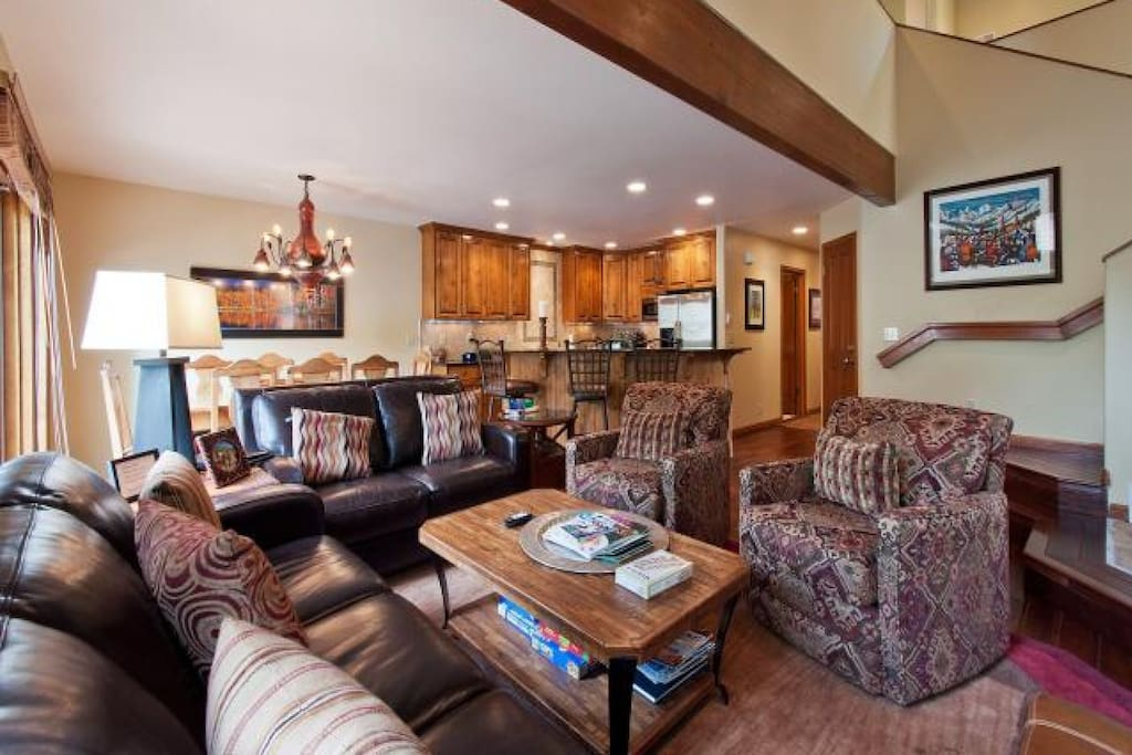 Large living room / great room that features leather furnishings, vaulted ceilings, hardwood mountain finishings that flows to the gourmet kitchen.