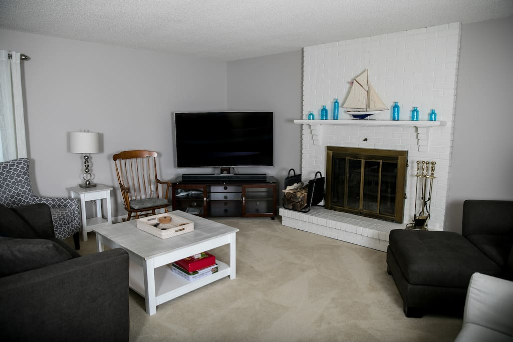 """View of back Family Room, with seating for the whole family, a wood fireplace, a Queen-sized sofa bed, and a 65"""" HDTV with premium sound bar."""