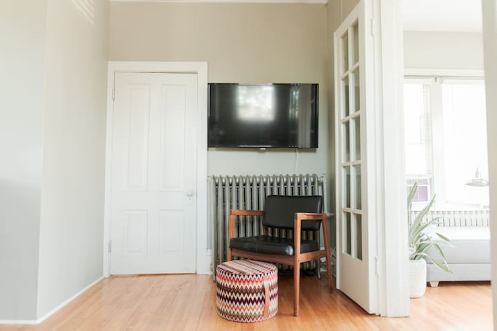View from the loveseat of TV with glimpse into bedroom through the French doors.  Cable TV can be enjoyed from dining area for four and the loveseat opposite.