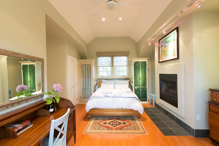 Beautiful private room with a fireplace, desk, seating area, and private bathroom.