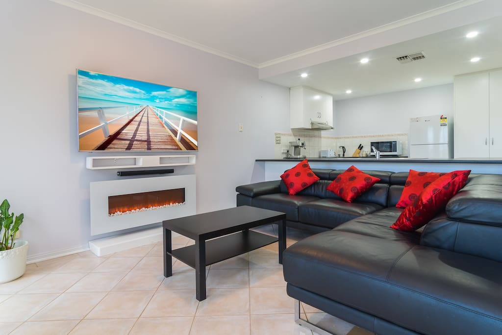 """Leather lounge, 65"""" UHD tv with blue tooth sound bar."""