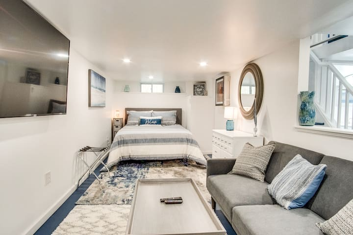 """Lower level area with memory foam Queen size bed and full size futon to watch 65"""" Smart Roku TV. Full staircase access from main level and backyard deck."""