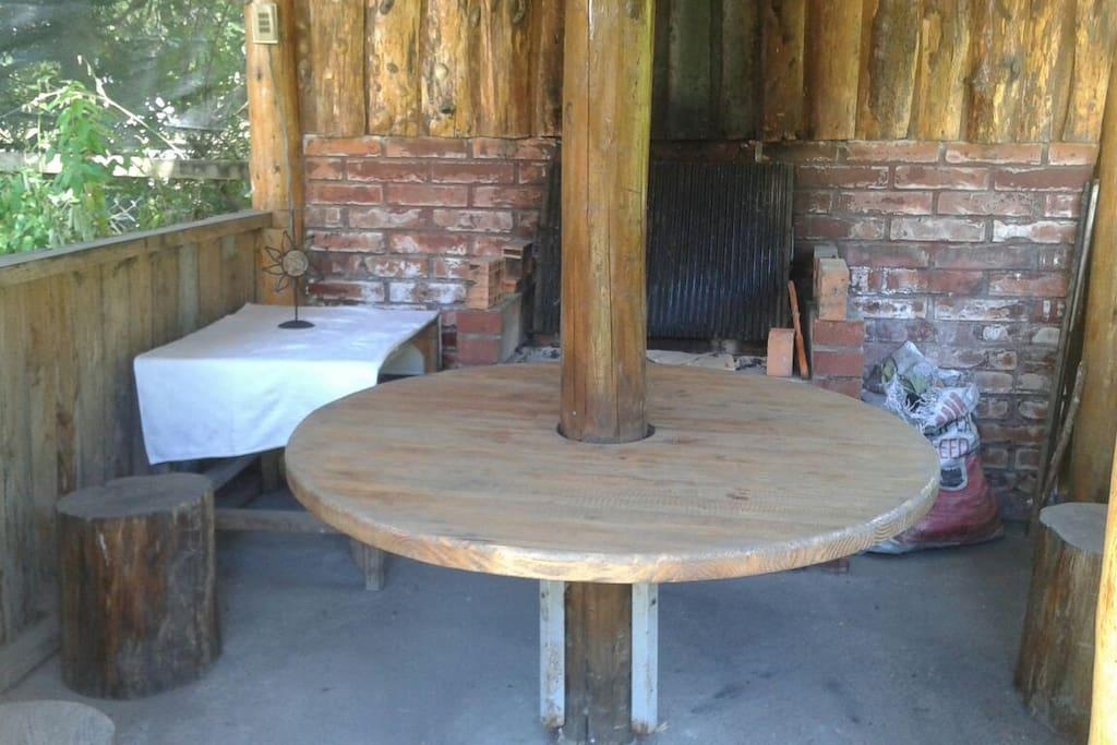 quincho con parrilla y asador mesa anexa y mesa redonda en el centro con pisos de troncos posee luz y enchufe