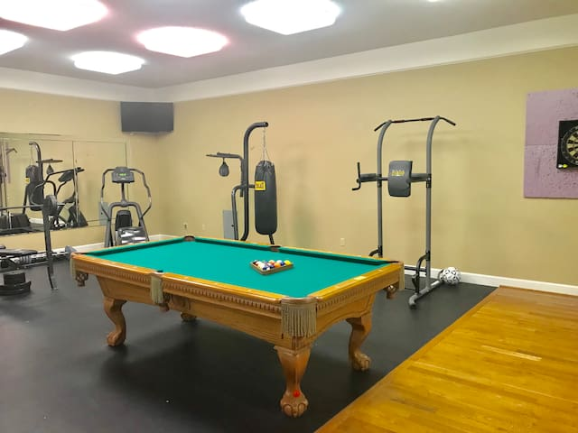 Weights and billiards with dart board and sports closet for fun.
