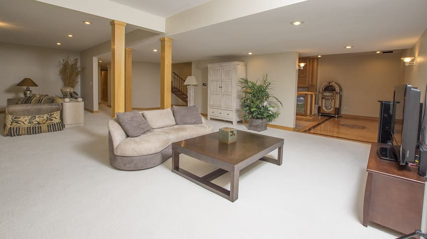 Small seating area with television on lower level next to family room and bar area