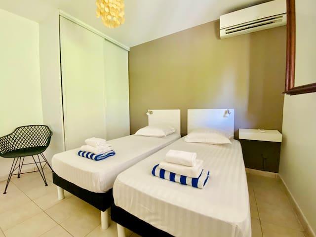 Chambre n°3 climatisée avec deux lits simples en 90cm (possibilité de faire un lit double 180cm), grande armoire, vue jardin