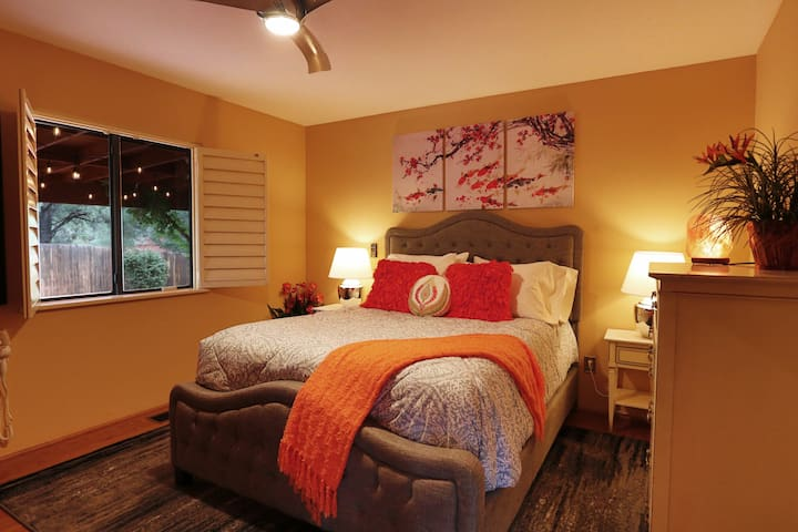 Queen bed in Fire-Opal room; view into landscaped backyard. Makeup mirror, blow dryer, desk/makeup table.