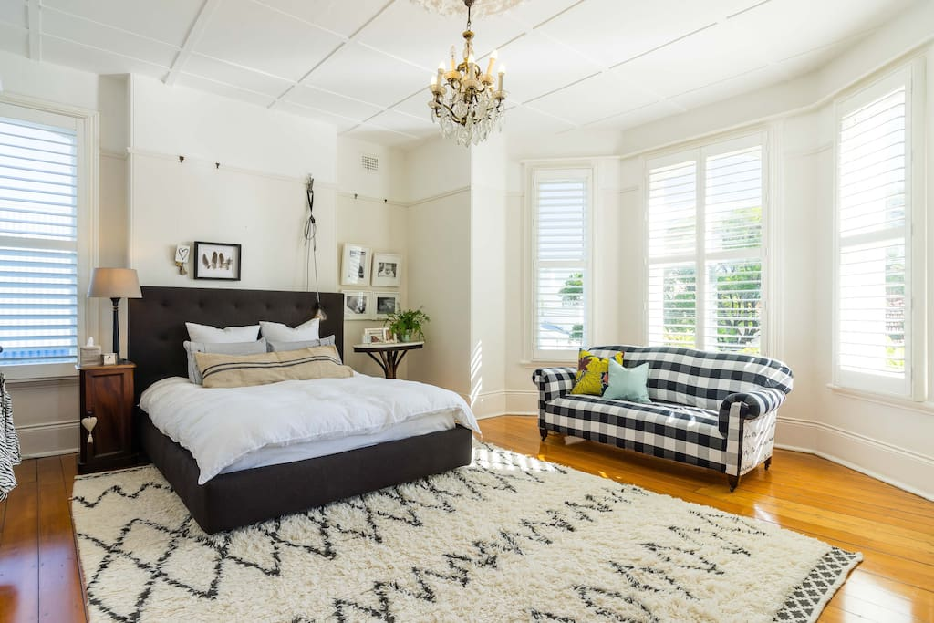 Large master bedroom with beautiful bay window and shutters
