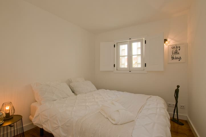 la chambre blanche avec sa fenêtre donnant sur les toits