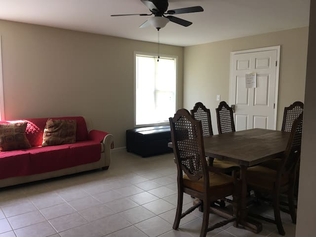 2nd living area with a dining table and queen size sofa sleeper and foldable ottoman sleeper in the basement