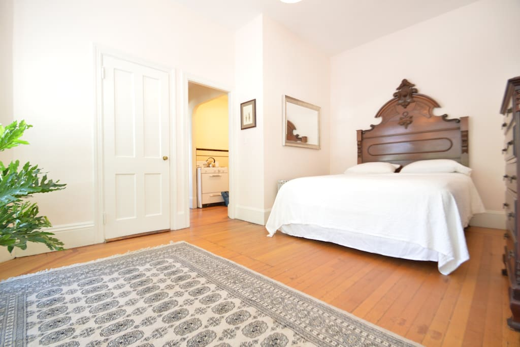 bedroom features a queen sized pillow top mattress bed with high quality cotton linens, antique headboard, dresser, closet, seating area, and luggage rack