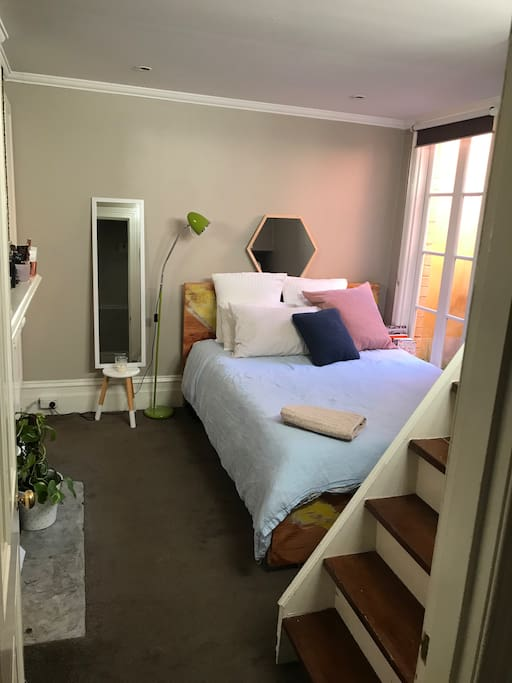 Bedroom 2: Large room with an upstairs loft/study retreat. High ceilings, beautiful atrium provides natural light all day. Queen Bed