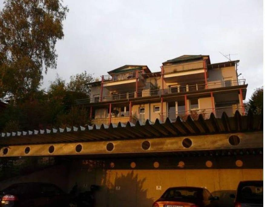 Außenansicht von unten. Die Wohnung oben links. Hanglage. Von oben 1.Obergeschoß