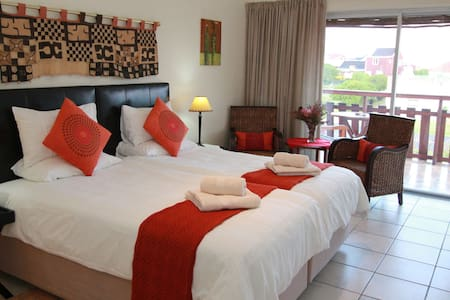 As you enter the Oystercatcher with a view of  extra seating within the suite and on the balcony overlooking Walker Bay.