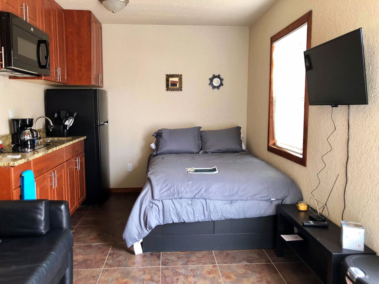 Small living room area with TV (antenna). Microwave, coffee maker, full size fridge. Futon couch and full size bed. Full bathroom.