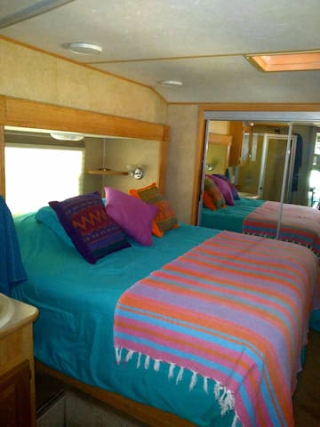 Trailer bedroom with queen bed, A.C, fan, closet, dresser and good ventilation.