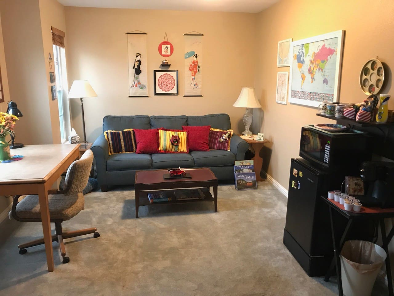 Welcome to your suite!  This view shows your cozy parlor, with coffee station, microwave and fridge, and sofa bed.
