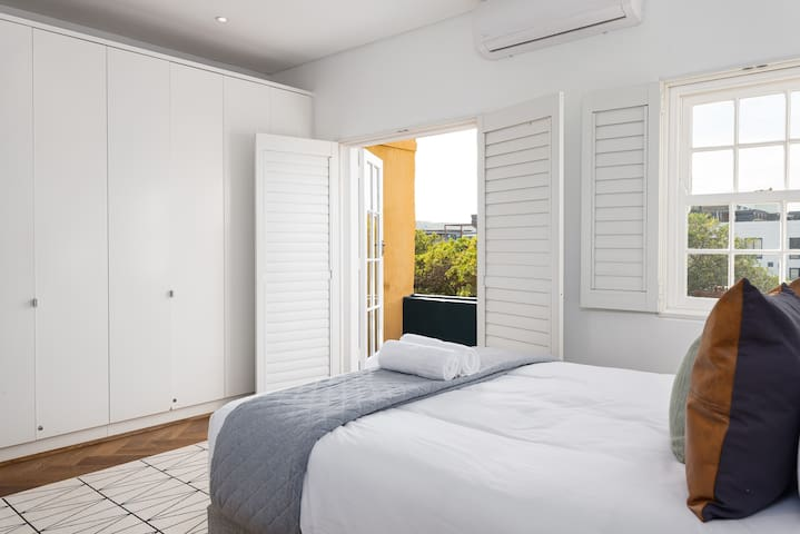 The master bedroom has plenty of cupboard space and beautiful shutters that lead out onto a private balcony
