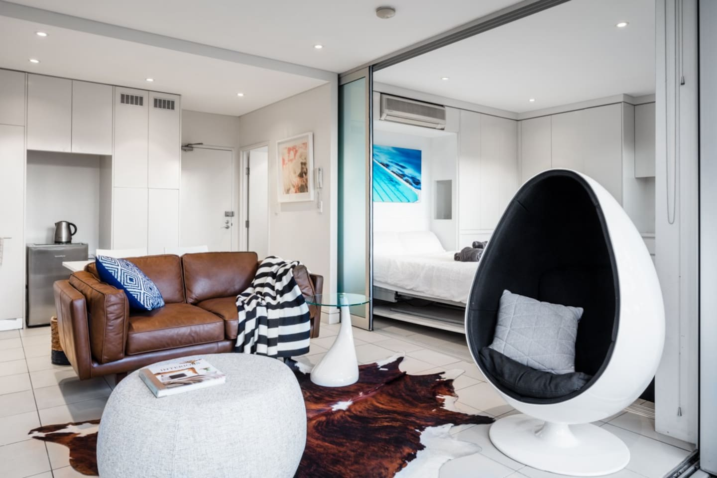 New leather sofa and designer egg chair, cowhide rug, sliding glass panel between living area and bedroom, new Daikin air conditioner (installed since photo taken), table and two chairs behind sofa.