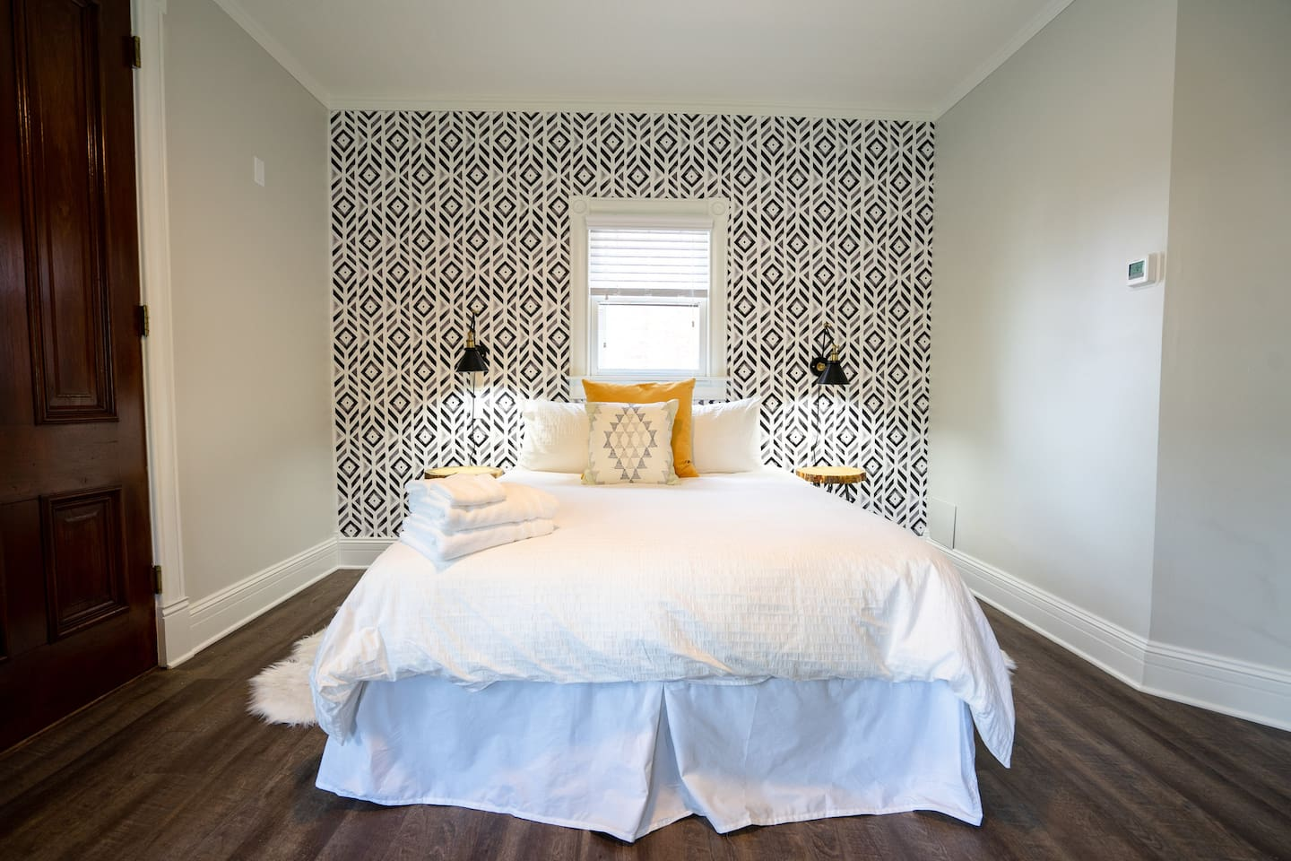 The room features a plush queen bed.