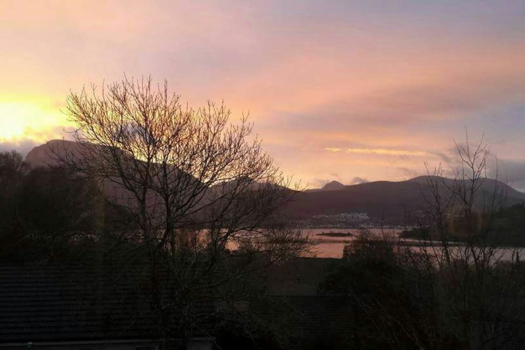The mountain on the left side is the view of Ben Nevis at sunrise . My house is south facing and also with loch views towards Fort William