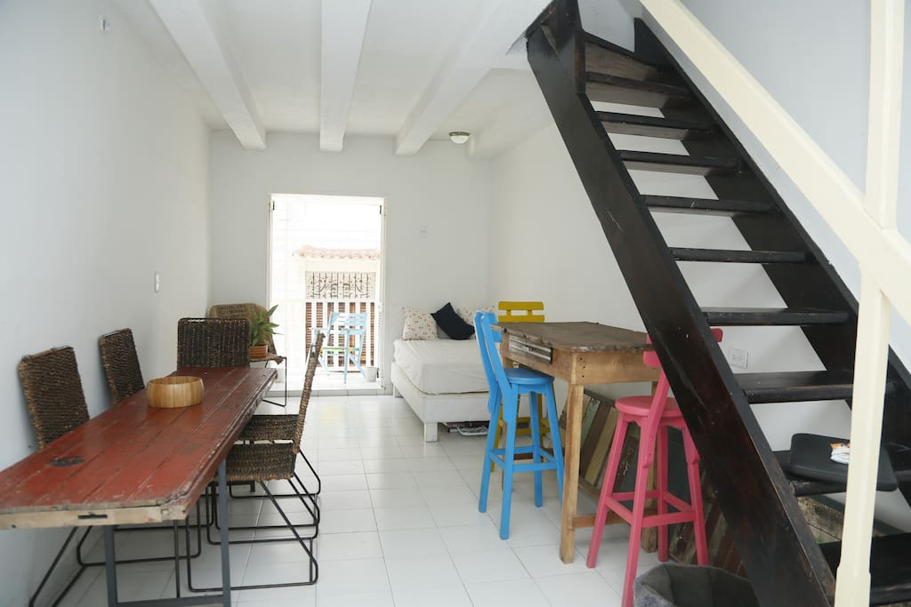 Large downstairs living room with worktop, table, daybed and street facing balcony.