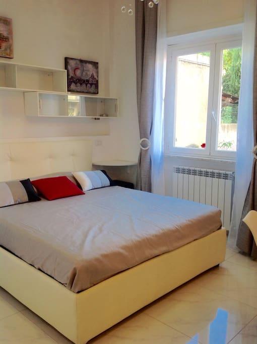 Zona notte con letto matrimoniale contenitore e materasso molto confortevole. Effetti luce sulla parete del letto.