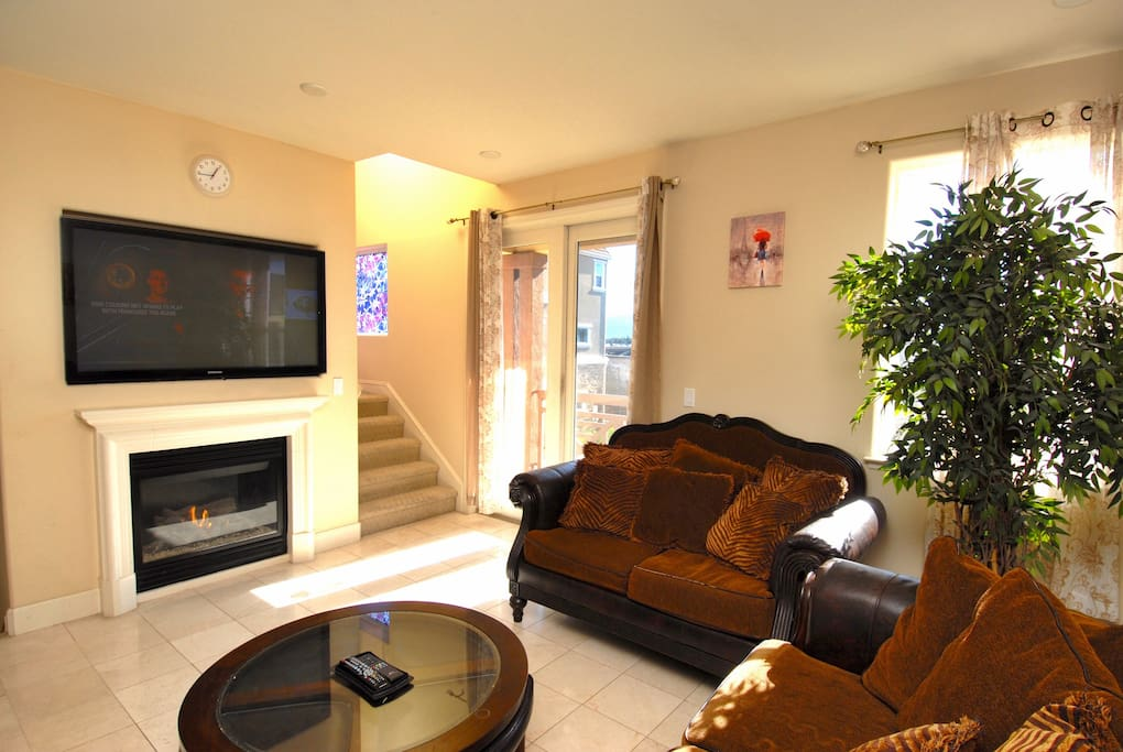 Comfy sofa and love seat facing the cozy fireplace and large screen cable TV